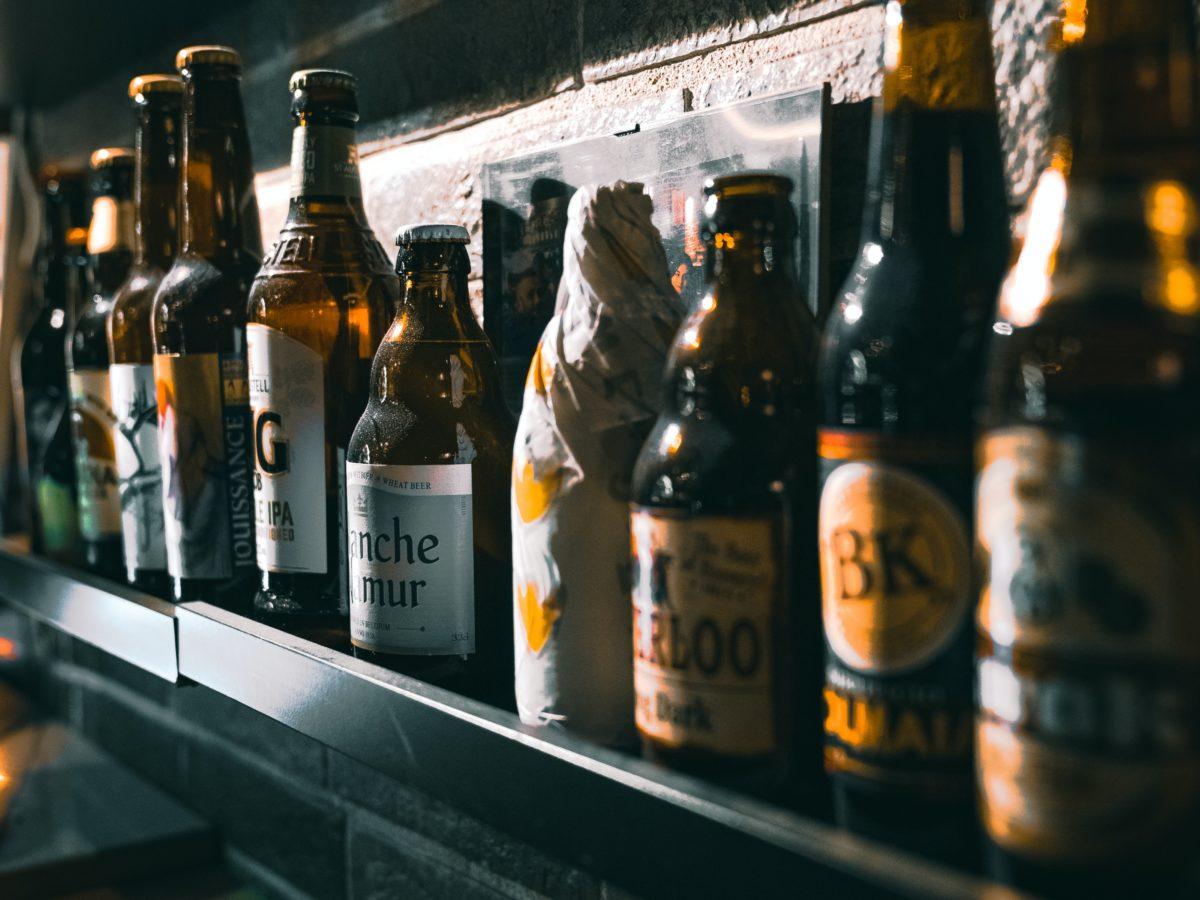 shallow focus photo of bottles on black wooden shelf