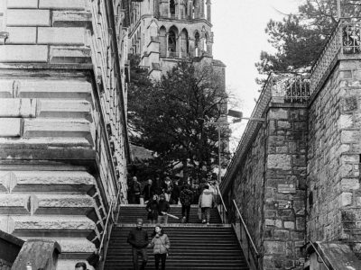 grayscale photo of people walking on stairs near building
